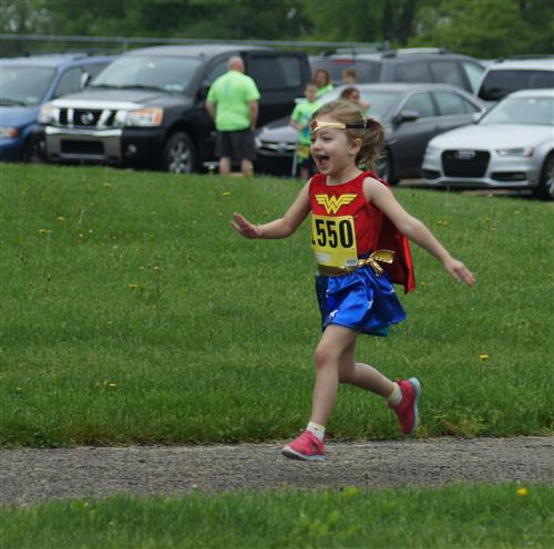Excited girl running in her Wonder Woman costume