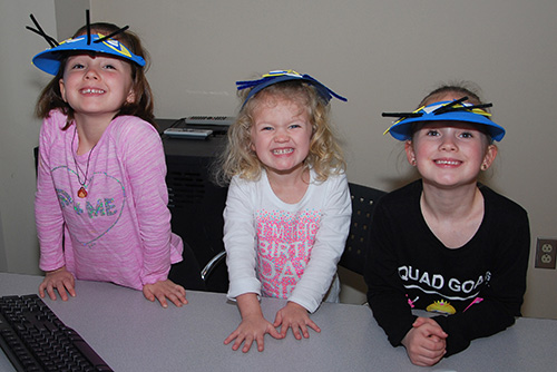 Three smiling girls with silly visors