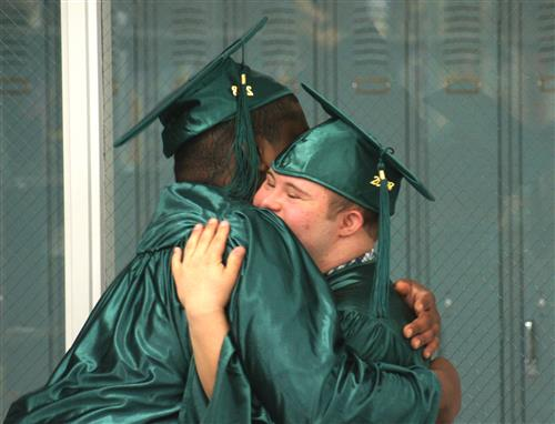 PRIDE students embrace at graduation.