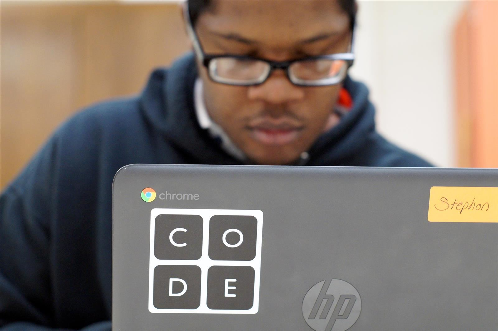 A student codes on his laptop during class.