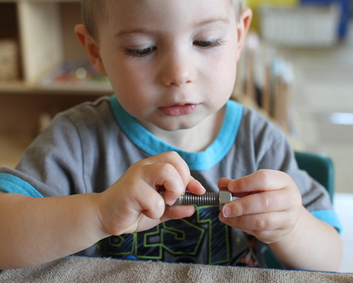 Toddler boy works on fine motor skills as he screws a nut onto a bolt