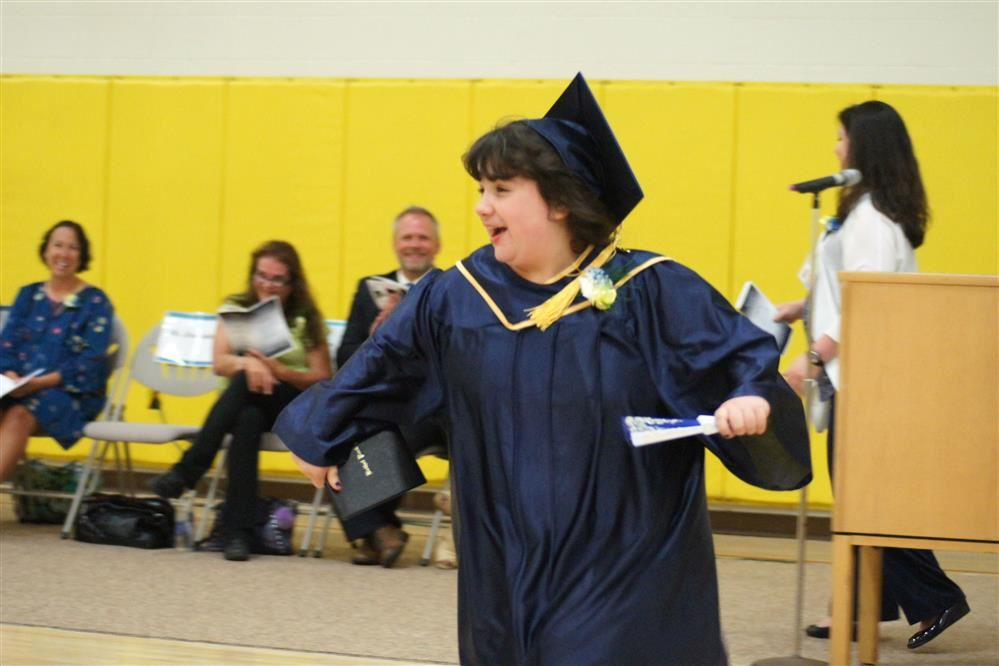 A Mon Valley student races to greet her mother after receiving her diploma.