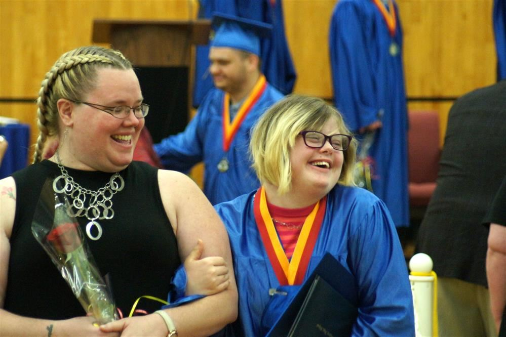 A Sunrise student, right, and her chaperone, left, walk down the aisle during the school commencement ceremony.