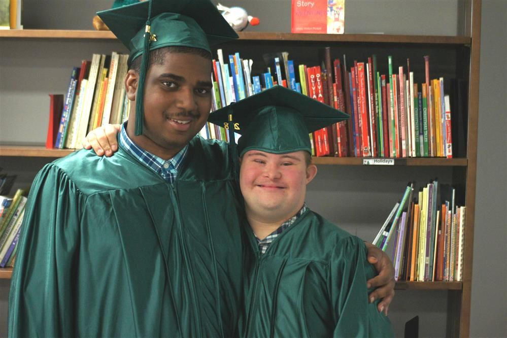Two Pathfinder students smile as they pose for a picture prior to graduation.