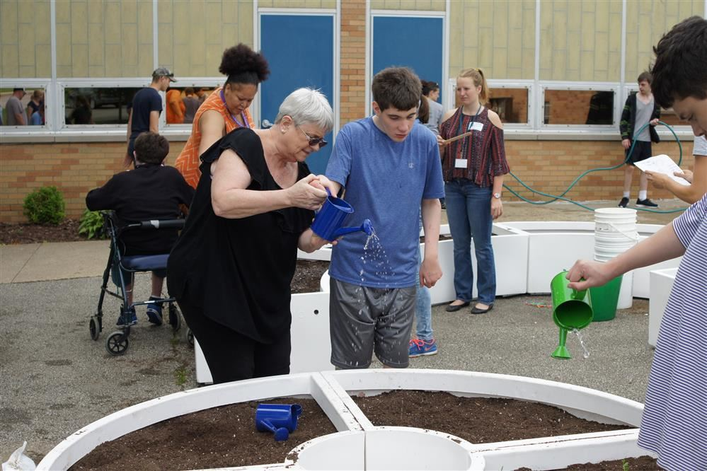 A Pathfinder student is assisted while he waters the school's learning garden.
