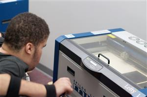 A student observes the laser cutter.