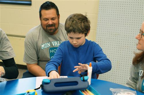 A teacher at Mon Valley helps a young student code.