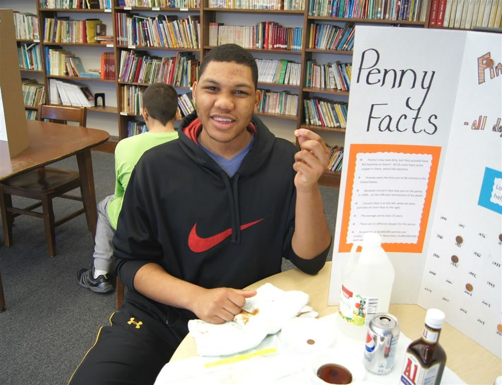 A Sunrise student shows off his science fair project during a presentation in the school library.