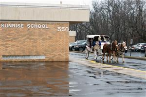 A horse-drawn carriage rides students along.